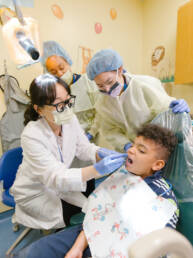 Pediatric Dentist and assistants Photographed working on patient