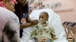 Little Girl getting oxygen in the ER being helped by nurse